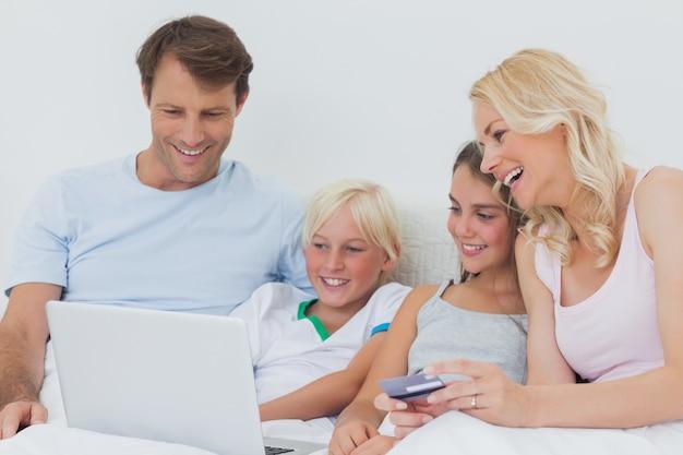 Famiglia utilizzando computer e carta di credito a letto