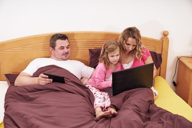 Famiglia che utilizza dispositivi digitali mentre giaceva a letto la mattina