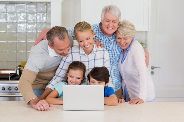 Famiglia che utilizza computer portatile nella cucina