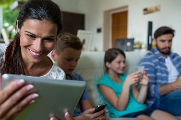 Famiglia che utilizza computer portatile e telefono cellulare nel salone