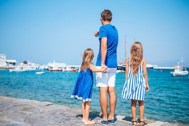 Vacanze in famiglia in europa. padre e figli sullo sfondo della città di mykonos in grecia