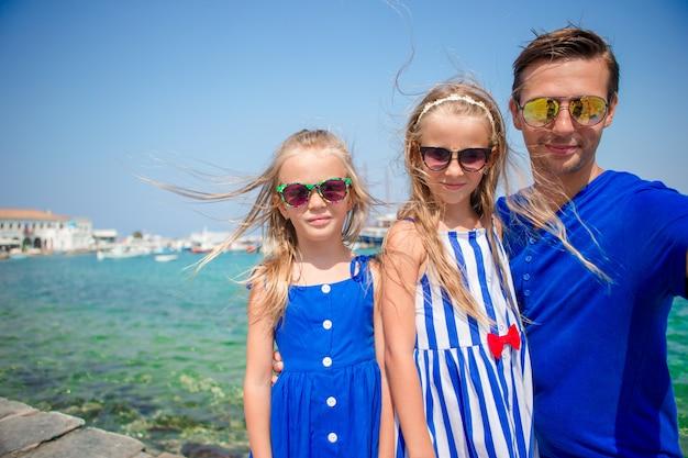 Vacanze in famiglia in europa. padre e figli prendendo selfie sulla città di mykonos in grecia
