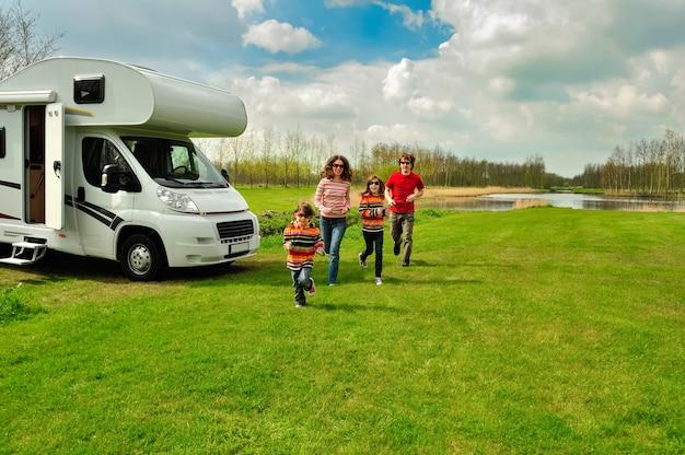 Vacanze in famiglia, viaggi in camper con bambini, genitori felici con bambini si divertono in viaggio di vacanza in camper