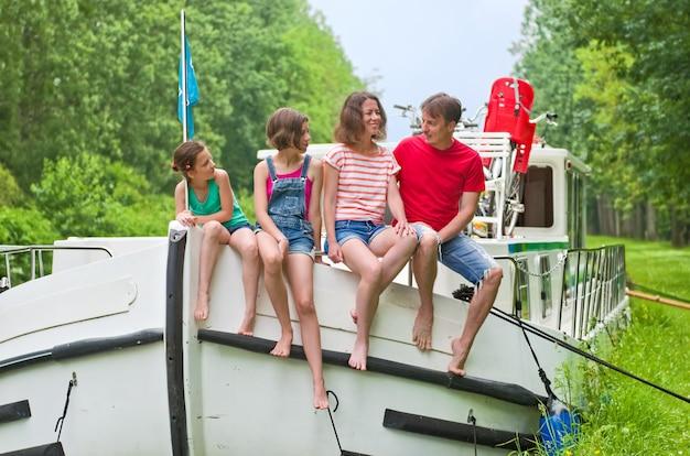 Vacanze in famiglia, viaggi di vacanze estive su una chiatta nel canale, bambini felici e genitori che si divertono durante il viaggio in crociera sul fiume in casa galleggiante in francia
