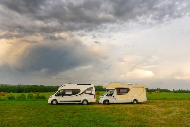 Vacanze in famiglia e viaggi (viaggio) all'aperto in camper (auto per roulotte). due camper in un campeggio estivo all'aperto. viaggia (viaggio) in auto concetto.