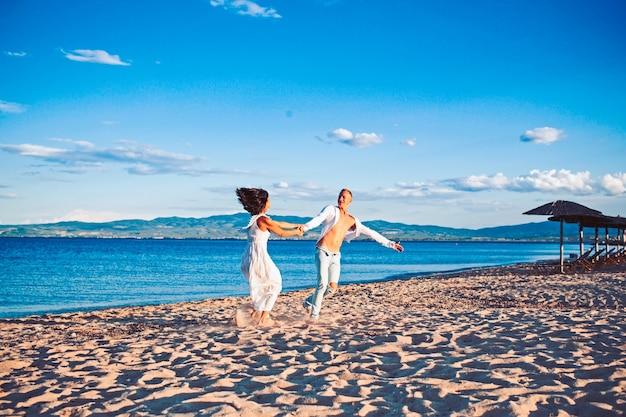 Famiglia e san valentino. vacanze estive e vacanze di viaggio. donna e uomo sexy in mare. coppia in amore ballare sulla spiaggia. ami le relazioni delle coppie danzanti che si godono insieme la giornata estiva.