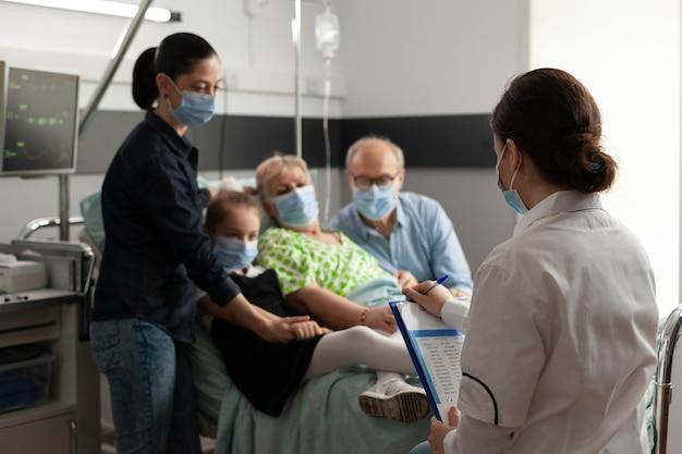 Famiglia che visita una donna anziana anziana mentre indossa una maschera protettiva