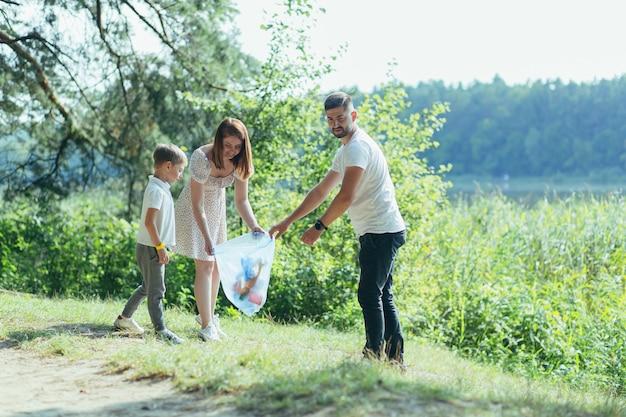 Il volontario della famiglia pulisce i rifiuti in natura. padre e madre, genitori, figli, figli volontari di famiglia in una giornata di sole che puliscono le bottiglie dei rifiuti nella foresta di detriti piegati in un sacchetto di plastica