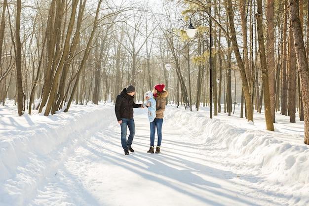 Passeggiata in famiglia in un parco invernale. bambino e madre e padre