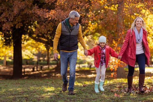 Famiglia che cammina al parco durante l'autunno