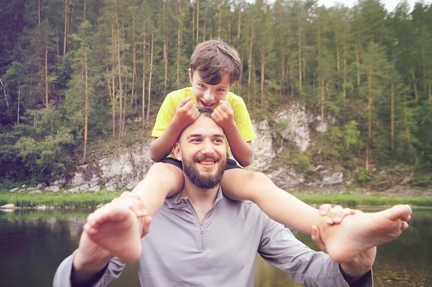 La famiglia cammina attraverso la foresta vicino al fiume, il padre porta suo figlio sulle spalle, l'ecoturismo, le attività ricreative all'aperto durante le vacanze estive.