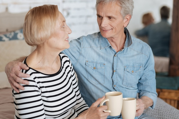 Calore familiare. persone dolci e perfette felici che condividono i loro pensieri mentre sono seduti sul letto e si godono un tè caldo