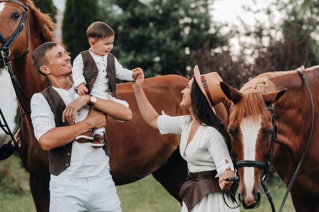 Una famiglia in abiti bianchi con il figlio sta vicino a due bellissimi cavalli nella natura. una coppia alla moda con un bambino viene fotografata con i cavalli.