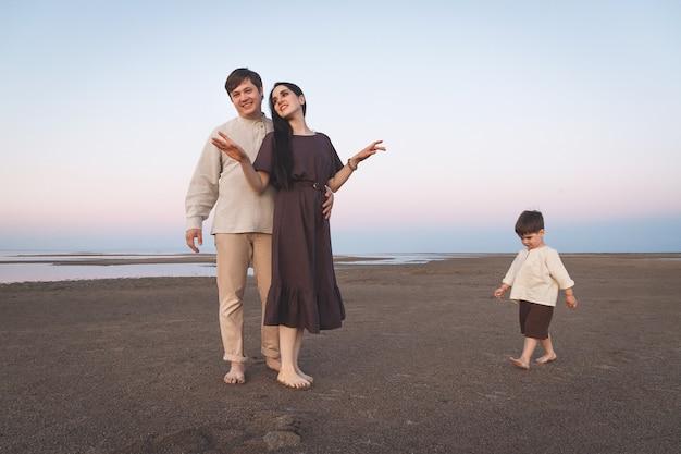 Famiglia con figlio di 3 anni cammina a piedi nudi lungo la selvaggia spiaggia serale vestiti di lino dall'aspetto familiare