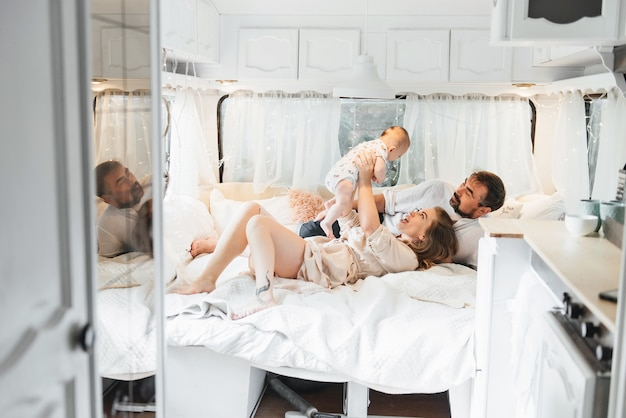Famiglia con bambino sul letto in roulotte al mattino