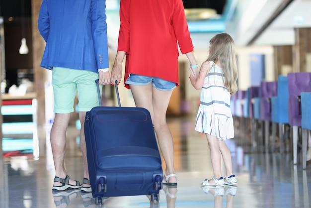 Una famiglia con un bambino sta rotolando la valigia