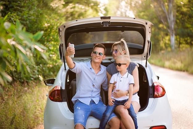 Famiglia con un bambino seduto nel bagagliaio di un'auto, preparandosi per una gita estiva al mare