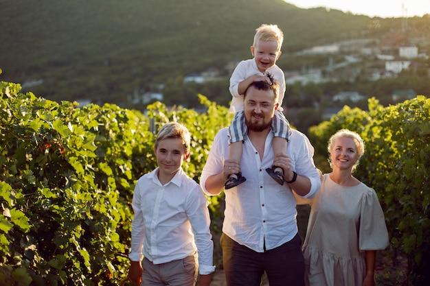 Famiglia con bambini ragazzo cammina in un campo di uva al tramonto con un cesto di bacche verdi