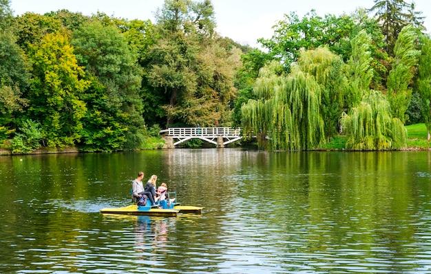 Famiglia con bambini su un catamarano in un laghetto del parco