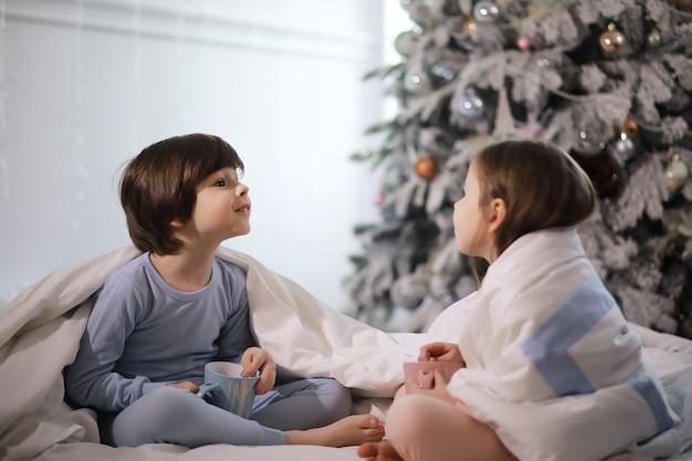 Una famiglia con bambini che si divertono sul letto sotto le coperte durante le vacanze di natale.