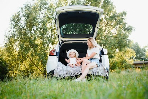 Famiglia con bambino seduto nel bagagliaio dell'auto