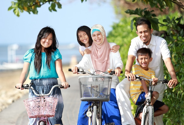 Le famiglie con bambini amano andare in bicicletta all'aperto in spiaggia