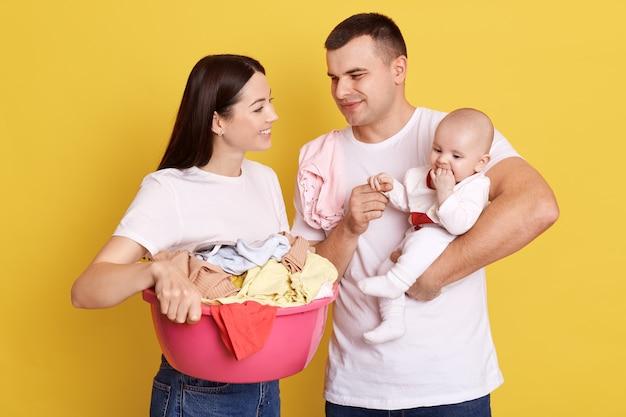 Famiglia con lavanderia isolata sopra la parete gialla, papà che tiene la piccola figlia neonata nelle mani, mamma in posa con il bacino pieno di vestiti sporchi, genitori in magliette casual bianche si prendono cura del bambino.