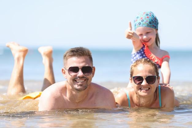 Famiglia con bambina sdraiata in mare