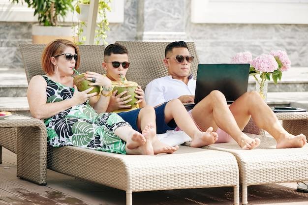 Famiglia con un bambino che si rilassa sulle sdraio a bordo piscina, madre e figlio che bevono cocktail di cocco quando il padre lavora al laptop