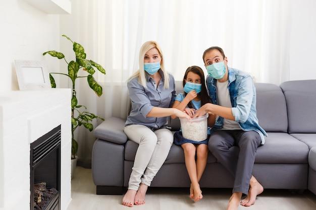 Famiglia con popcorn sul divano guardare la tv a casa. resta a casa durante la quarantena