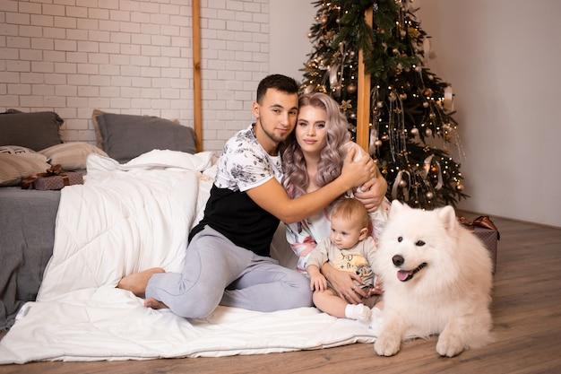 Famiglia con cane samoiedo seduto sul pavimento vicino al letto di casa sull'albero di natale sullo sfondo