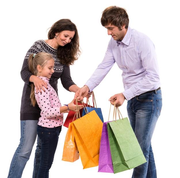 Famiglia con borse della spesa su un muro bianco