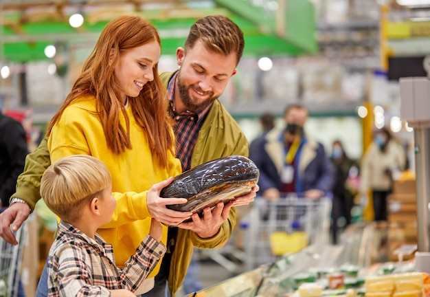 Famiglia con figlio che compra verdura fresca, scegli la migliore, donna discute l'acquisto con il marito