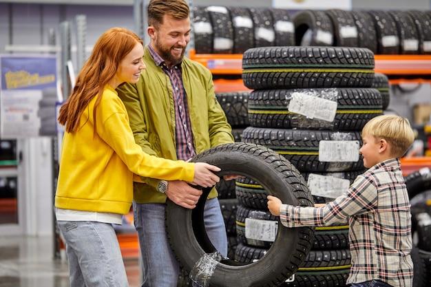 Famiglia con figlio che sceglie pneumatici per auto in negozio, fare la scelta insieme, divertirsi, concetto di acquisto