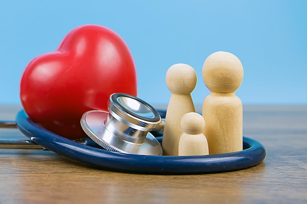 Famiglia con stetoscopio e un cuore rosso. concetti di esame fisico e assicurazione sanitaria.