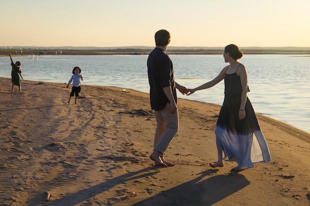 Una famiglia con due bambini sta passeggiando lungo una spiaggia selvaggia serale.
