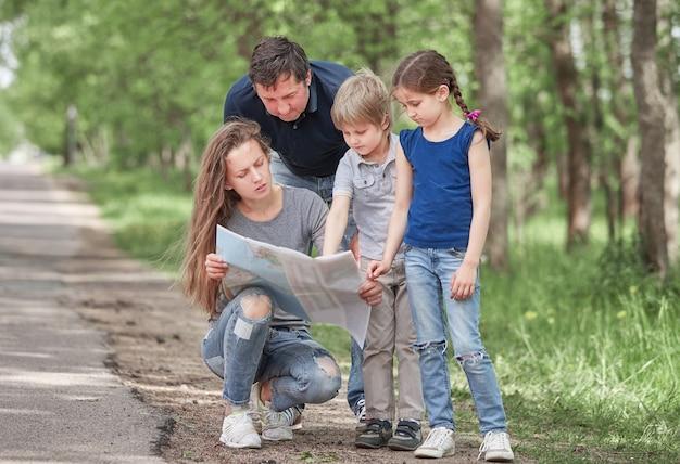 La famiglia con due bambini usa la carta durante il viaggio. buon tempo