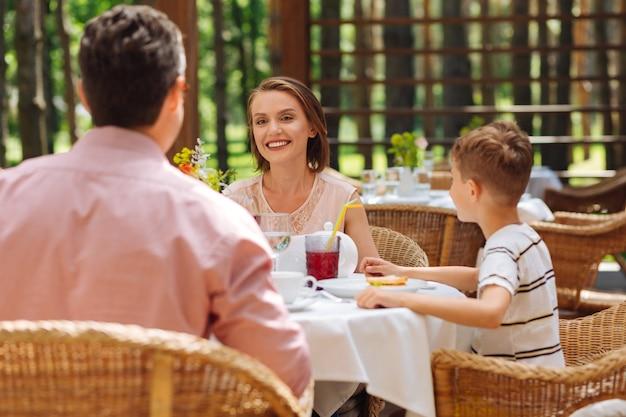 Donna di famiglia. trasmissione via ir di donna di famiglia guardando il marito e il figlio mentre discute i piani per il prossimo fine settimana