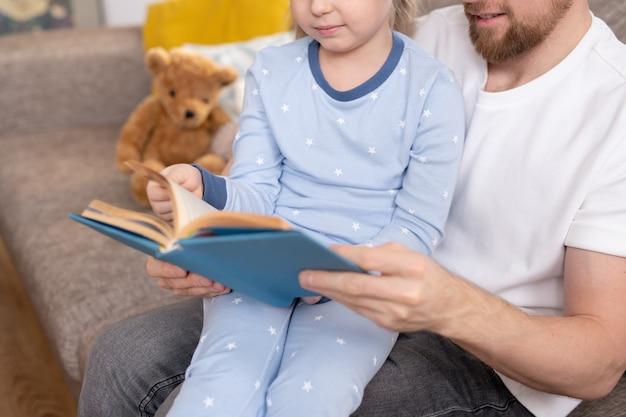 Famiglia di giovane padre e la sua adorabile piccola figlia in pigiama blu leggendo un libro interessante mentre ci si rilassa a casa prima di dormire