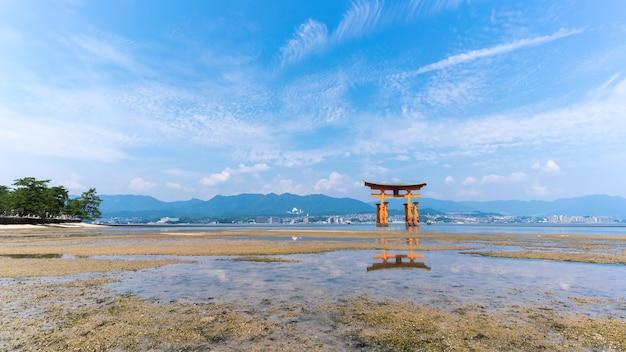 La famosa porta shintoista giapponese galleggiante arancione (torii) del santuario di itsukushima con riflessione , isola di miyajima della prefettura di hiroshima, giappone