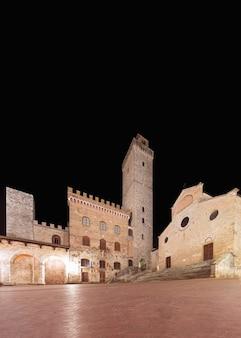 Famosa piazza del duomo di notte a san gimignano, toscana, italia.