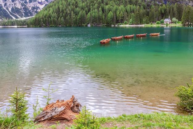Famose imbarcazioni da diporto in legno e piccola cappella sul lago di braies nelle alpi italiane