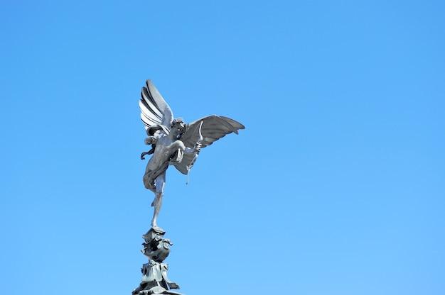 Statua famosa, cupido, nei precedenti del cielo blu al circo di piccadilly, londra