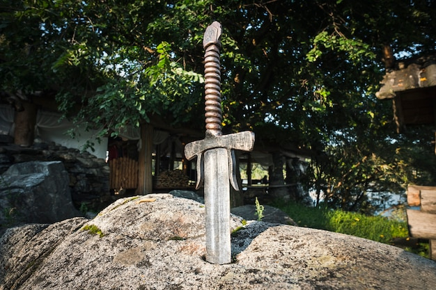 Famosa spada excalibur di re artù conficcata nella roccia. armi da taglio della leggenda pro re artù.