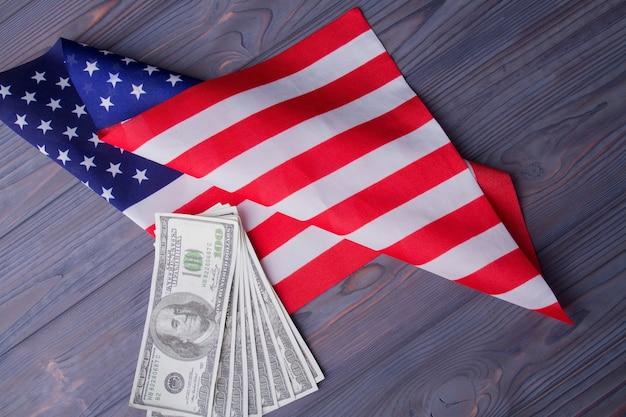 Fan di banconote in dollari e bandiera degli stati uniti sulla scrivania in legno