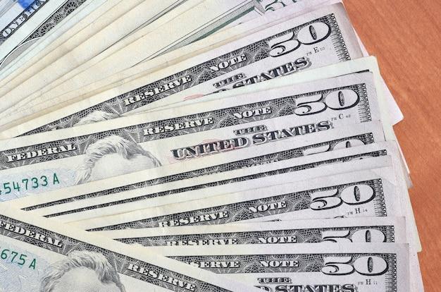 Fan di molte cento e cinquanta banconote in dollari sulla fine di legno della superficie del fondo su. vista dall'alto piatta. concetto astratto di affari
