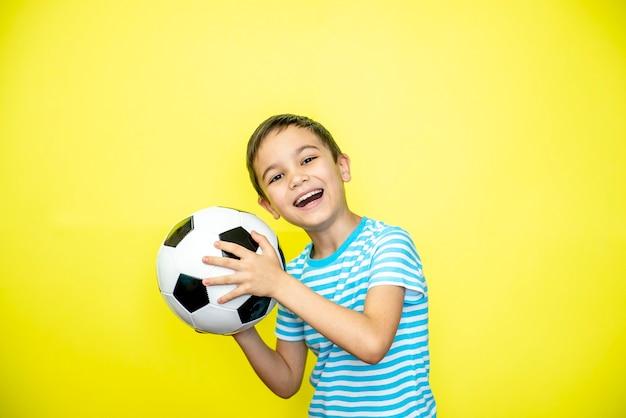 Il giocatore del ragazzo sportivo del fan tiene il pallone da calcio in maglietta a strisce che celebra la risata sorridente felice mostra il pollice
