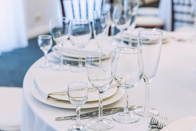 Fancy table set per la cena con bicchieri di tovagliolo in ristorante, sfondo interni di lusso