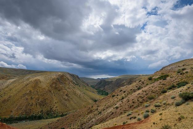 Fantastico paesaggio deserto. montagne multicolori contro il cielo coperto da nuvole con raggi di sole. colline rosse e marroni. repubblica dell'altaj, siberia, russia.