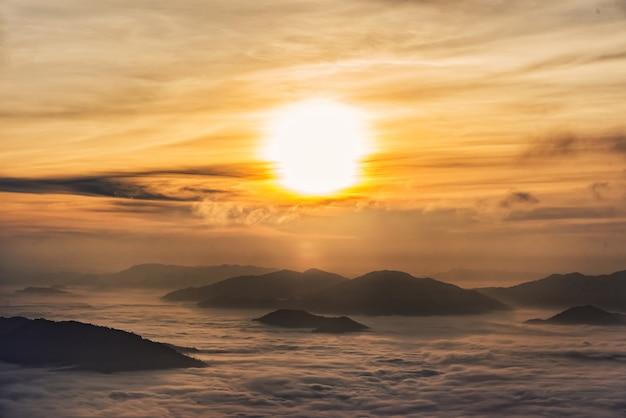Fantastica alba da sogno sulla cima della montagna rocciosa con vista in valle nebbiosa